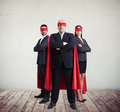 Two businessmen and businesswoman in superhero costume