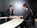 Two businessmen discussing tasks sitting at office table Royalty Free Stock Image