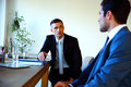 Two businessmen discussing tasks sitting at office table Stock Images