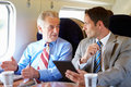 Two businessmen having meeting on train talking Royalty Free Stock Photo