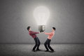 Two businessmen holding bright light bulb Royalty Free Stock Photography