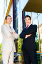 Two businessmen serious with arms crossed standing outdoors Royalty Free Stock Image