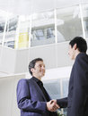Two businessmen shaking hands in office low angle view of atrium Royalty Free Stock Photography