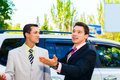 Two businessmen talking about cars standing and with one of them having expression on his face Stock Image