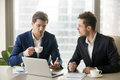 Two businessmen talking, sitting at office desk with laptop coff Royalty Free Stock Photo