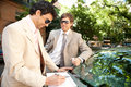 Two businessmen working leaning luxury car tree lined street city Stock Photos
