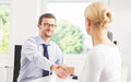 Two businesspeople in office with a handshake Royalty Free Stock Photo