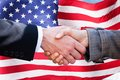 Two businesspeople shaking hands close up of in front of american flag Royalty Free Stock Image