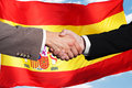 Two businesspeople shaking hands close up of in front of spanish flag Royalty Free Stock Images