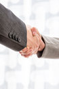 Two businesspeople shaking hands close up view of the arms of in suits over a blurred abstract background conceptual of a deal Stock Photos
