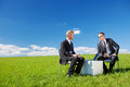Two businesspersons sitting and talking in green meadow Stock Images