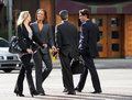 Two businesswomen and businessmen chatting whilst crossing street Stock Photos