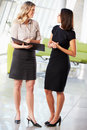 Two Businesswomen Having Informal Meeting In Modern Office Stock Photos