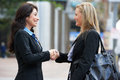 Two businesswomen shaking hands outside office smiling Stock Photo