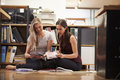 Two Businesswomen Sit On Office Floor With Digital Tablet Royalty Free Stock Photo