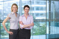 Two businesswomen standing beside large window in office, arm in arm, smiling, portrait Royalty Free Stock Photo