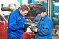 Two car mechanic diagnosing auto engine problem Royalty Free Stock Photography