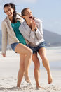 Two carefree women laughing and enjoying the beach portrait of Stock Photography