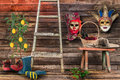 Two carnival masks hanging wall bottom wooden bench wicker b