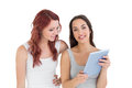 Two casual young female friends with digital tablet portrait of against white background Stock Photos