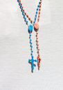 Two catholic rosary with crucifix a blue and a rose and a white textile on the background Stock Photos