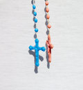 Two catholic rosary with crucifix close up a blue and a rose and a white textile on the background Royalty Free Stock Photos