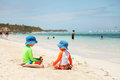 Two caucasian boys playing with sand at tropical beach Royalty Free Stock Photo