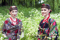 Two caucasian slavonic women sitting in the field of flowers wild Royalty Free Stock Images