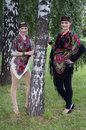 Two caucasian slavonic women standing near the birch tree in national costumes Stock Photo
