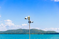 Two CCTV surveillance cameras on the sea and mountain background Royalty Free Stock Photo