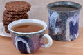Two ceramic tea cups and cookies pile of Royalty Free Stock Images