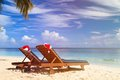 Two chair lounges with red santa hats on tropical summer beach Stock Photos