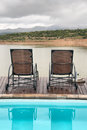 Two chairs between swimming pool and lake in mountains shot in a game lodge near oudtshoorn western cape south africa Royalty Free Stock Photography