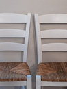 Two chairs with woven seats white ladder chair back rafia Stock Image