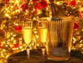 Two champagne flutes and a champagne bottle in a glass ice bucket in front of a Christmas tree. Royalty Free Stock Photo