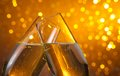 Two champagne flutes with gold bubbles on dark light bokeh background Royalty Free Stock Photo
