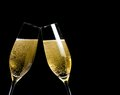Two champagne flutes with golden bubbles make cheers on black background space for text Stock Image