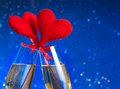 Two champagne flutes with golden bubbles and red velvet hearts make cheers on blue bokeh background space for text concept of Stock Image