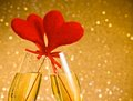 Two champagne flutes with golden bubbles and red velvet hearts make cheers on golden bokeh background space for text concept Stock Photography
