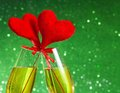Two champagne flutes with golden bubbles and red velvet hearts make cheers on green bokeh background space for text concept Royalty Free Stock Photos
