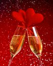 Two champagne flutes with golden bubbles and red velvet hearts make cheers on red bokeh background concept of valentine day Stock Photos