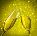 Two champagne flutes with golden bubbles on yellow light bokeh background make cheers Stock Images
