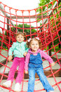 Two charming girls on net of playground red in summer Stock Photos