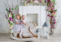 Two charming little girls play in the light room decorated with flowers. Baby girls swinging on a wooden horse Royalty Free Stock Photo