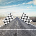 Two checker flags crossed road with yellow arrow with Stock Photos