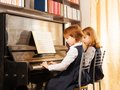 Two cheerful beautiful small girls playing piano Royalty Free Stock Photo