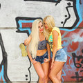 Two cheerful blondes having fun on the background of the transition to the metro Royalty Free Stock Photography