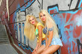Two cheerful blondes having fun on the background of the transition to the metro Stock Image