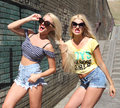 Two cheerful blondes having fun on the background of the transition to the metro Royalty Free Stock Photo