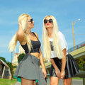 Two cheerful blondes having fun on the background of the transition to the metro Stock Images